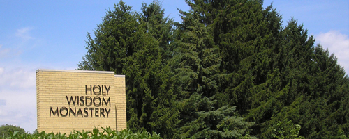 Holy Wisdom Monastery driveway sign in front of tall evergreen trees