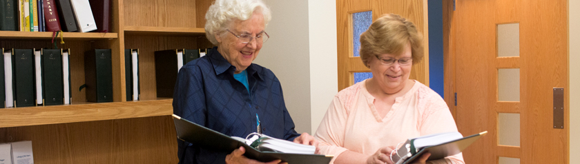 Sister Joanne and retreatant looking together at prayer books used for daily prayer