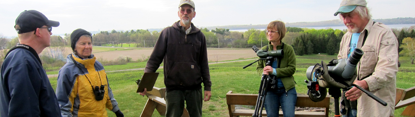 A group of bird-watchers gathered on the monastery hilltop overlooking Lake Mendota.