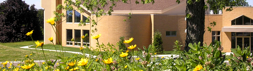 Front door and windows of Holy Wisdom Monastery seen through yellow spring flowers blooming in the surrounding prairie