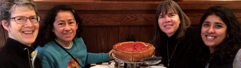 4 sisters gathered around deep dish pizza