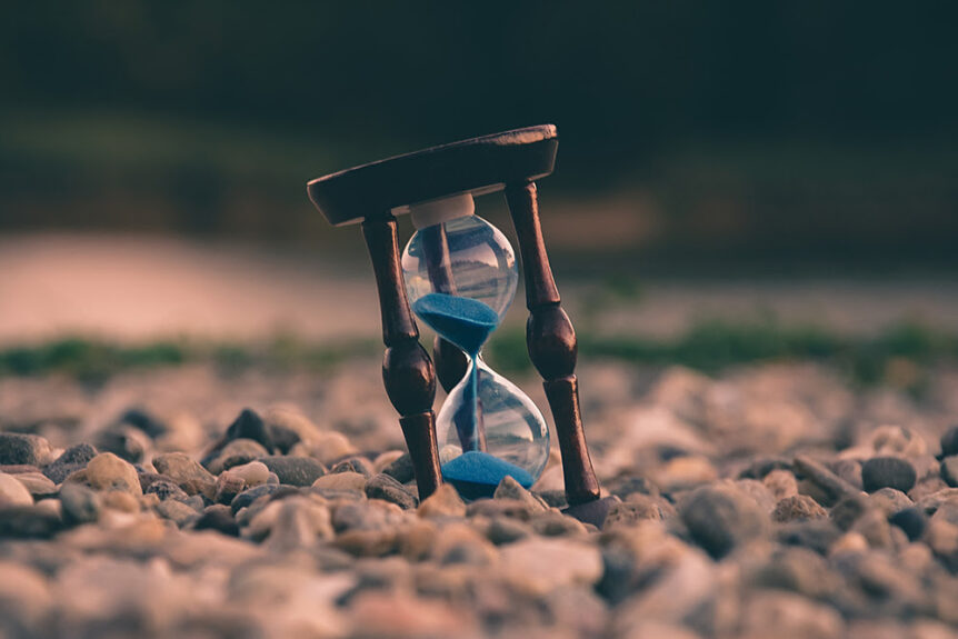 Hourglass on the ground with sand halfway to the bottom