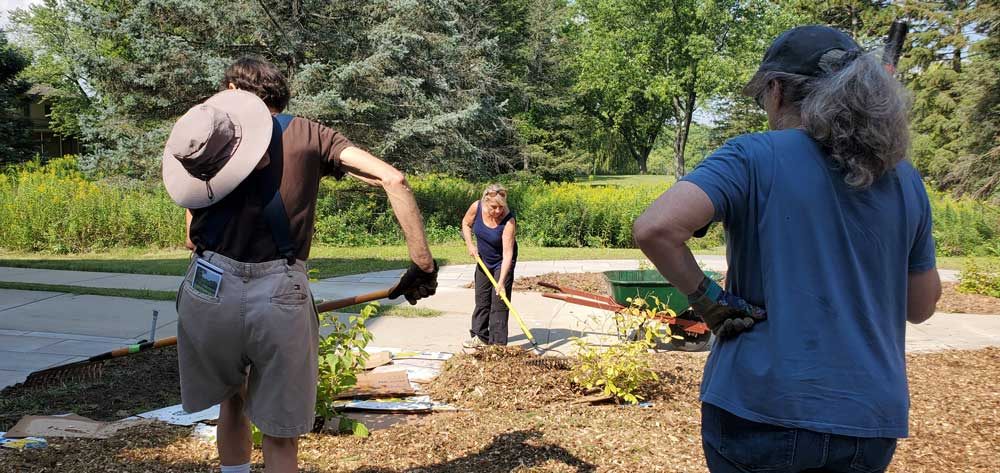 Three volunteers working in the Memorial Courtyard. Two have rakes and are spreading woodchips. One is resting.